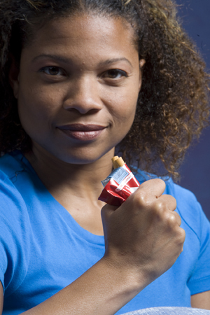 Woman crushing pack of cigarettes in hand.