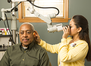 Healthcare provider examining man's ear with scope.