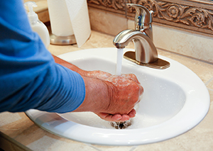 Closeup of man's hands washing with soap in sink.