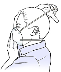 Man putting upper strap of dust mask over his head.
