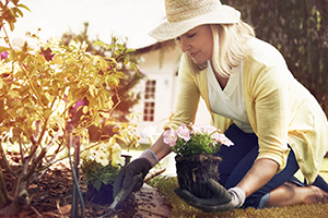 Woman wearing a hat and planting flowers in the yard