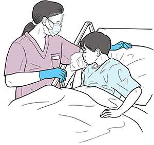Boy in hospital bed coughing into tissue. Healthcare provider standing beside bed wearing face shield, mask and gloves.