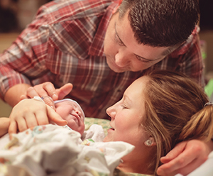 Couple in hospital holding their newborn baby.