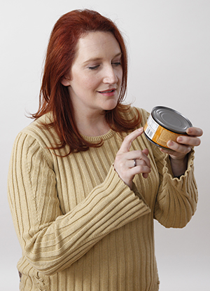 Woman reading nutrition label on can.