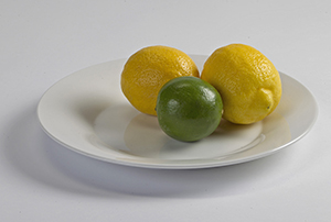 Two lemons and a lime on plate.