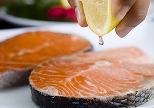 Closeup of hand squeezing lemon juice onto salmon steak.